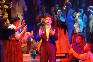The cast surrounds Andrew Pollis (as Harry Houdini) in the opening number.