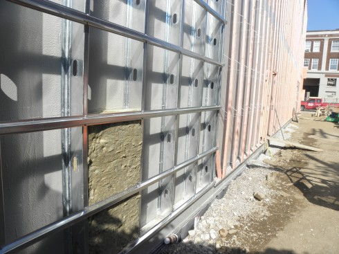 An initial piece of insulation occupies a niche in the metal-framed part of the south wall, outside the elevator shaft.